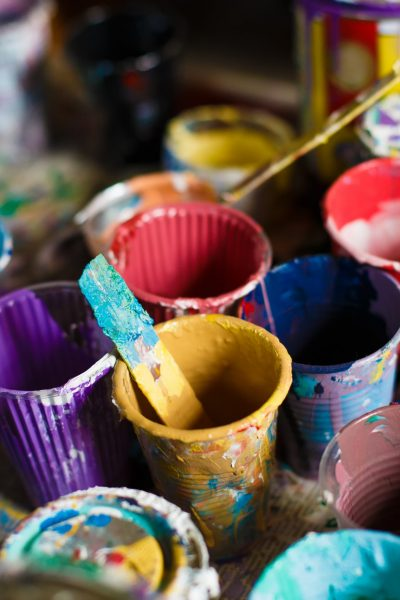 Multicolored plastic cans with paints. Artist workplace background. Old dirty Paints background. Colorful artist palette. Soft toned. Creativity, visual art concept. Art and craft.